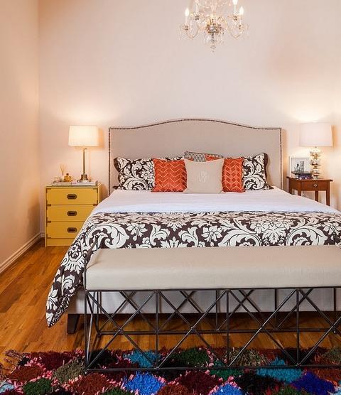 разные прикроватные тумбы и столики возле одной кровати